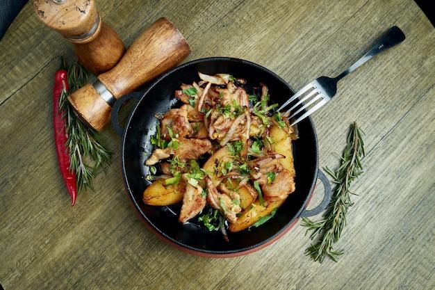 Pommes de terre sautées au bacon, oignons et herbes dans une poêle décorative sur un. vue de dessus sur la nourriture savoureuse.