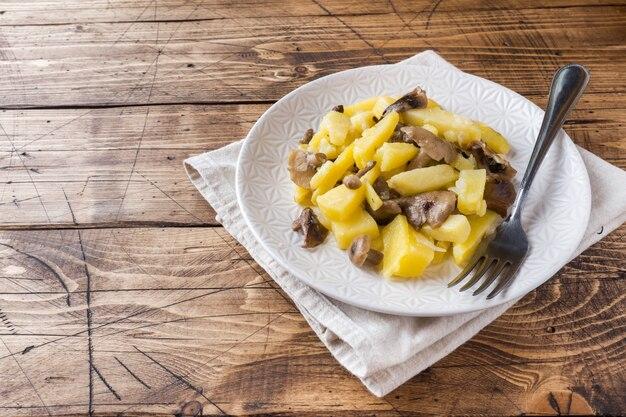 Pommes de terre sautées aux champignons et aux oignons. table en bois.