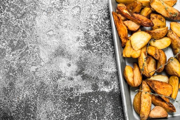 Pommes de terre sautées sur une plaque à pâtisserie avec des épices et des herbes sur table rustique.