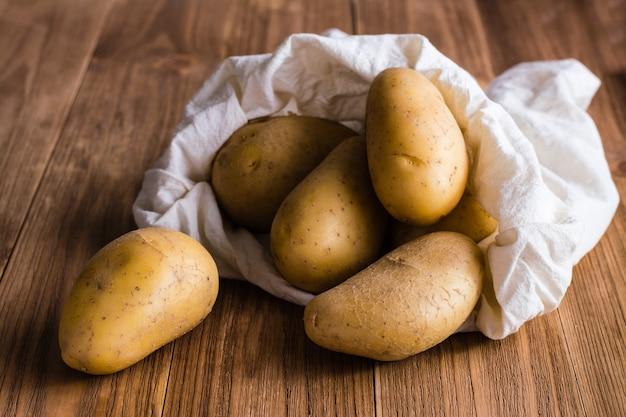 Les pommes de terre sont coulées du sac sur une table en bois