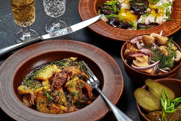 Pommes de terre avec de la viande et des œufs frits à l'oignon avec des boudins et des cornichons sur la table