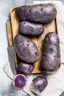 Pommes de terre violettes crues sur une planche à découper. vue de dessus.