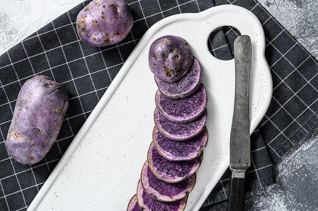 Pommes de terre violettes tranchées crues sur une planche à découper blanche. vue de dessus