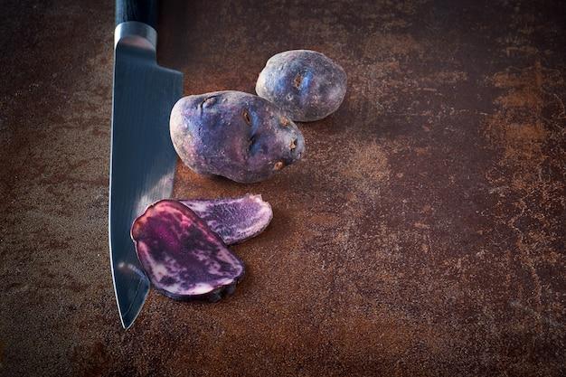 Pommes de terre vitelotte tranchées, trois tranches sur couteau et deux pommes de terre entières sur noir