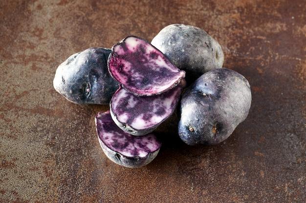 Pommes de terre vitelotte tranchées, trois tranches et trois pommes de terre entières sur fond noir