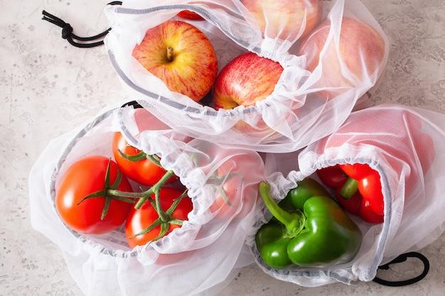 Pommes tomates poivrons légumes dans un sac en nylon à mailles réutilisable, concept zéro déchet en plastique gratuit