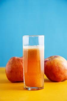 Pommes et un verre de jus de pomme naturel sur jaune-bleu