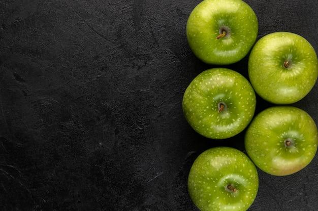 Pommes vertes aigres entières parfaitement formées de fruits moelleux juteux sur fond gris