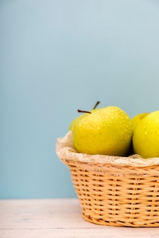Pommes vertes biologiques dans un panier sur une surface en bois.
