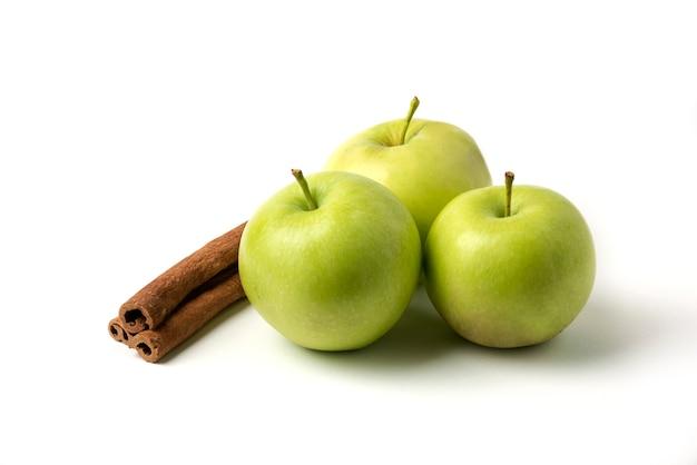 Pommes vertes et cannelles isolés sur blanc