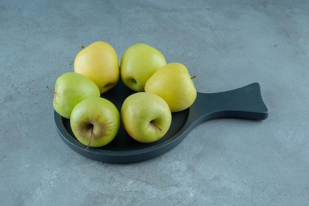 Pommes vertes sur une casserole, sur le fond de marbre.