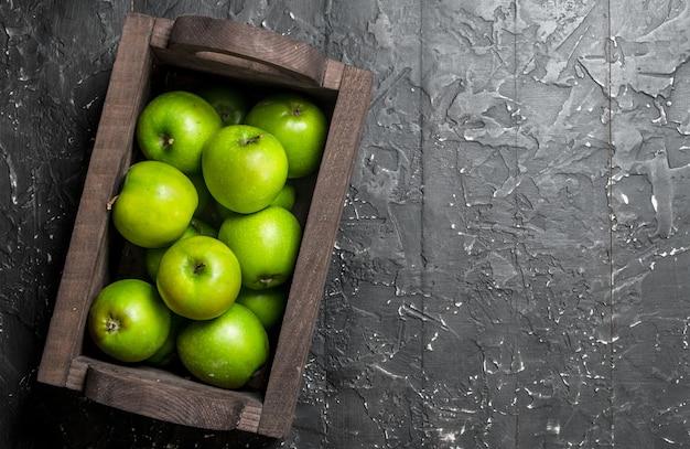 Pommes vertes dans une boîte en bois. sur un fond en bois sombre.