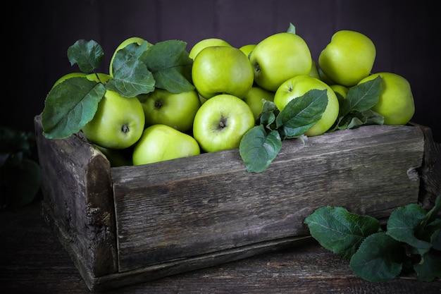 Pommes vertes dans une boîte en bois sur de vieilles planches, rustique, vintage, récolte