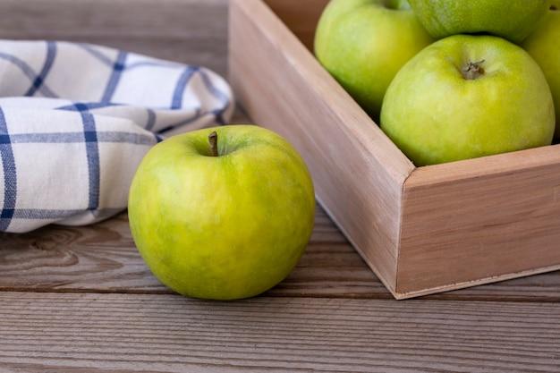 Pommes vertes dans une boîte sur une table en bois