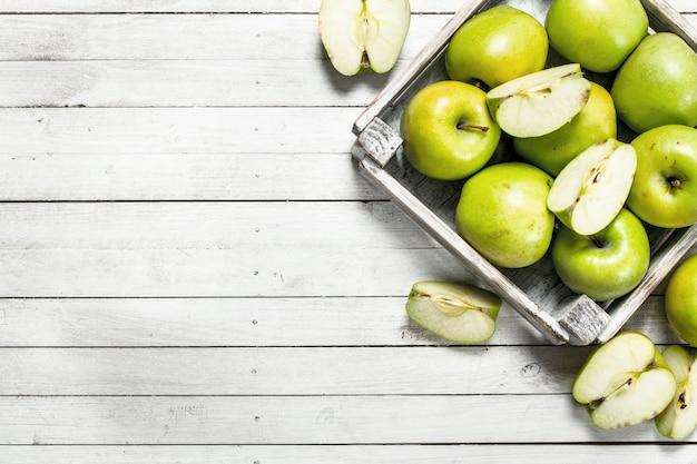 Pommes vertes dans une petite boîte. sur un fond en bois blanc.