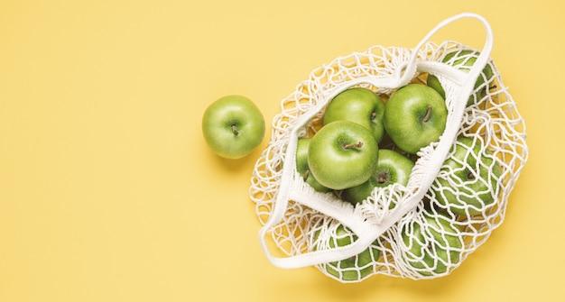 Pommes vertes dans un sac en filet avec fond jaune pastel