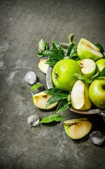 Pommes vertes dans une tasse avec de la glace. sur une table en pierre rustique.