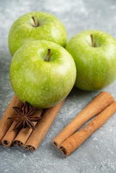 Pommes vertes entières et bâtons de cannelle sur table en marbre.