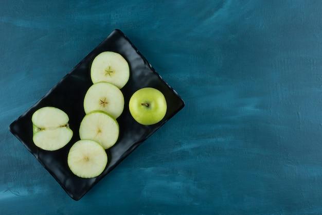 Pommes vertes entières et tranchées placées sur un plateau sombre.
