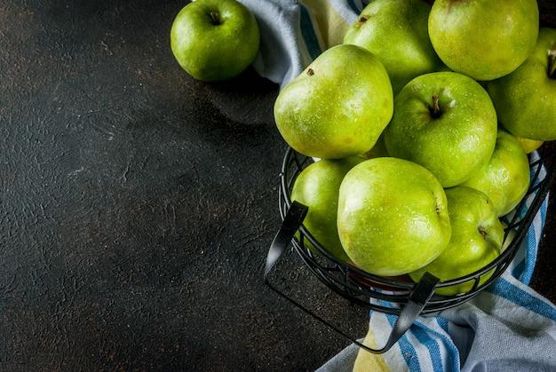 Pommes vertes de ferme biologiques crues fraîches dans un panier en métal noir, rouillé foncé, fond