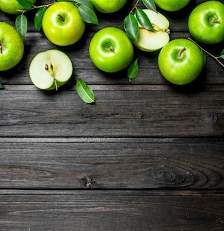 Pommes vertes avec des feuilles et des tranches de pomme. sur fond en bois.