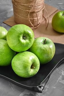 Pommes vertes sur fond gris avec un sac en papier pour la livraison, la livraison de nourriture, l'emballage environnemental.