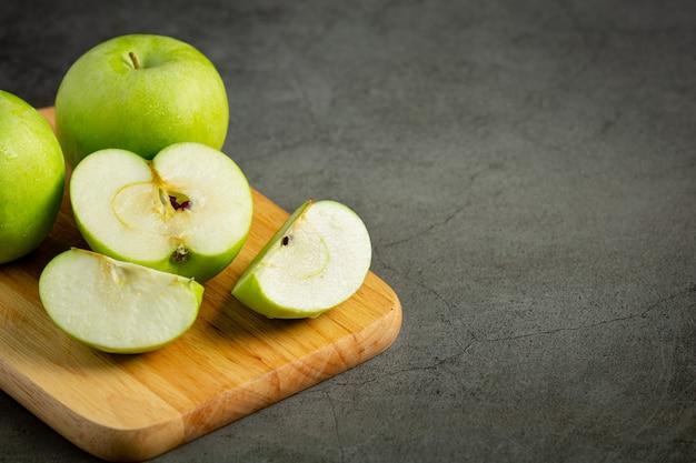 Pommes vertes fraîches coupées en deux mises sur une planche à découper en bois