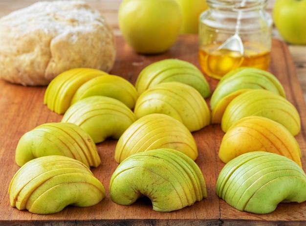 Pommes vertes fraîches coupées en tranches sur une planche de bois