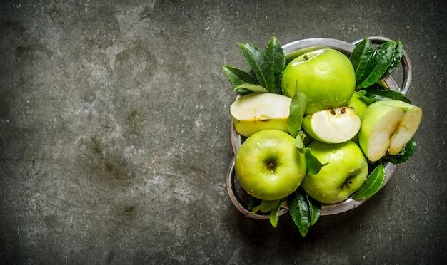Pommes vertes fraîches avec des feuilles dans la tasse. sur une table en pierre rustique. espace libre pour le texte. vue de dessus