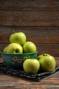 Pommes vertes fraîches avec des gouttes d'eau sur eux dans un bol bleu