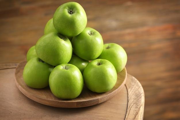 Pommes vertes fraîches sur plaque en bois