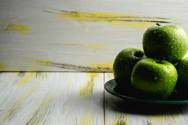 Pommes vertes fraîches sur une vieille table en bois. alimentation saine et écologique. harmonie des couleurs