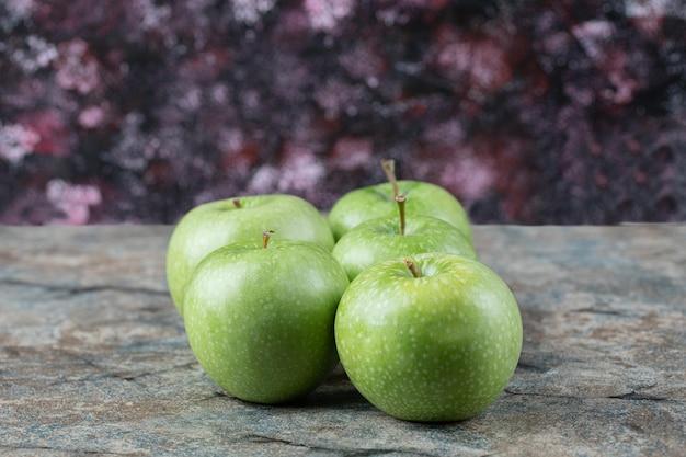 Pommes vertes isolées sur béton.