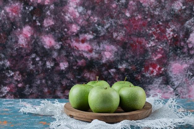 Pommes vertes isolées sur planche de bois.