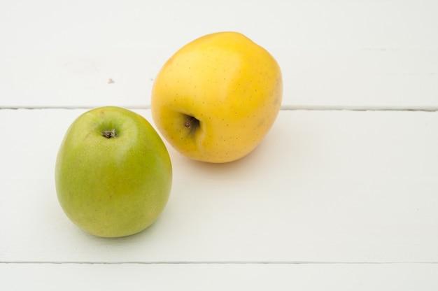 Pommes vertes et jaunes sur un fond en bois blanc