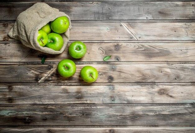 Pommes vertes juteuses dans un vieux sac. sur fond de bois gris.