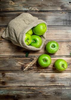 Pommes vertes juteuses dans un vieux sac. sur une table en bois gris.