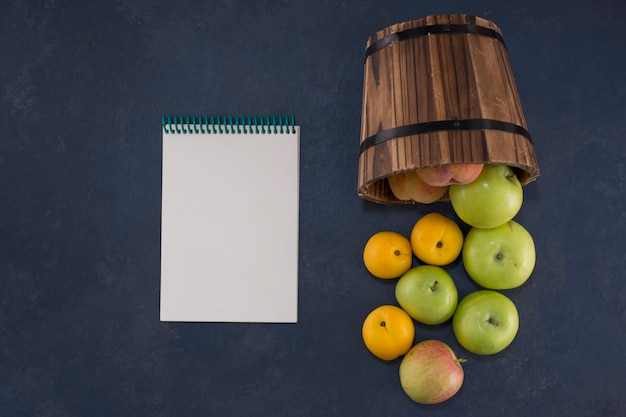 Les pommes vertes et les oranges d'un seau en bois sur fond noir avec un ordinateur portable de côté