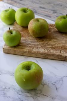 Pommes vertes sur une planche de bois pour trancher
