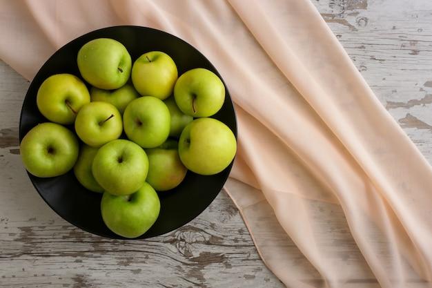 Pommes vertes sur une plaque noire
