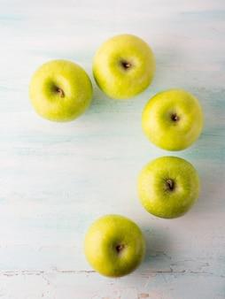 Pommes vertes point d'interrogation sur la table blanche turquoise