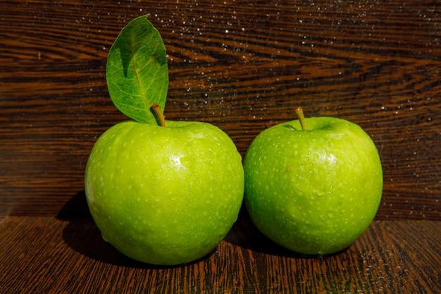 Pommes vertes rosées avec des feuilles sur bois incurvé foncé humide, vue latérale.