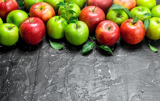 Pommes vertes et rouges entières avec des feuilles. sur fond rustique noir.