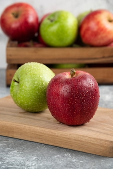 Pommes vertes et rouges entières humides sur une planche à découper en bois.