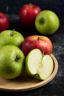 Pommes vertes et rouges entières et tranchées sur plaque de bois.