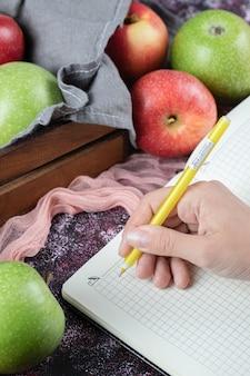 Pommes vertes rouges et un livre de recettes vérifié