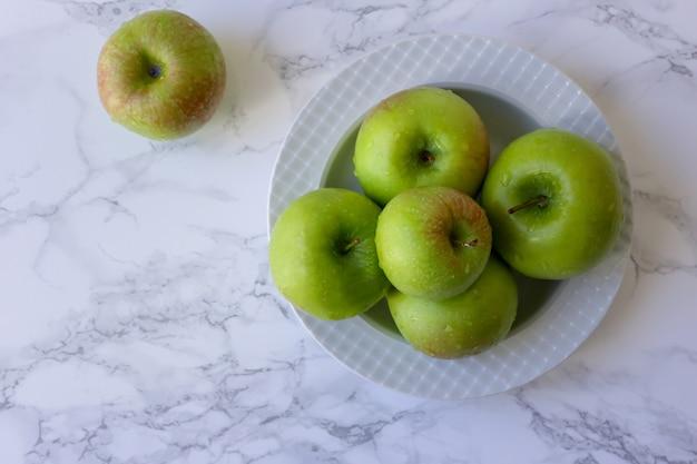 Pommes Vertes Et Saines Dans Une Assiette Blanche Sur La Table De Cuisine Photo Premium