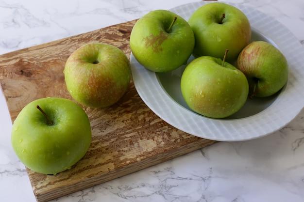 Pommes vertes et saines dans une assiette blanche sur la table de cuisine