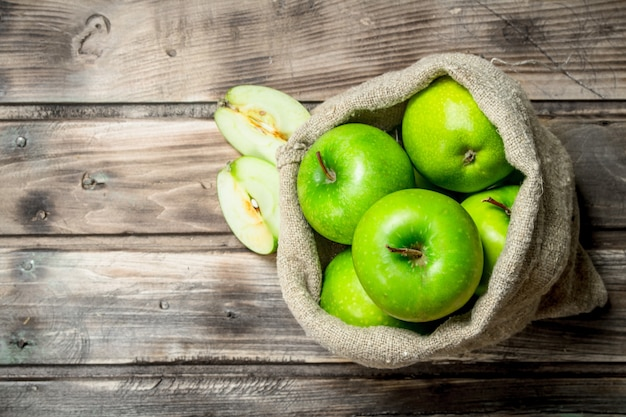 Pommes vertes et tranches de pomme dans un vieux sac.