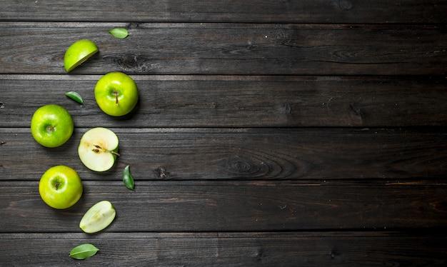 Pommes vertes et tranches de pomme. sur un fond en bois sombre.